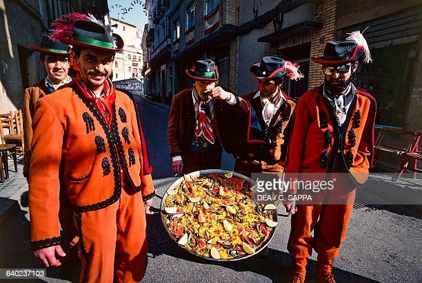 Men in traditional costumes carrying a paella pan Moors and Christians festival Bocairente Valencia Spain