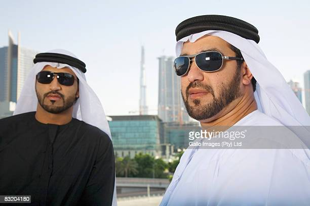 Men in traditionally Middle Eastern attire looking earnestly at camera, Dubai cityscape in background, UAE