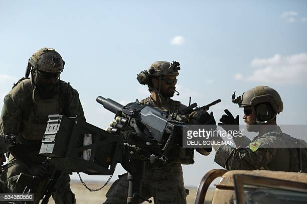 Men in uniform identified by Syrian Democratic forces as US special operations forces ride in the back of a pickup truck in the village of Fatisah in...