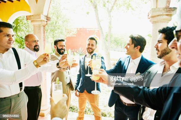 men in wedding party sharing a toast before ceremony at luxury resort - mid adult stock pictures, royalty-free photos & images