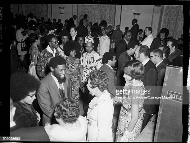 Men including one wearing dashiki and matching cap and women shaking hands with C DeLores Tucker and others in William Penn Hotel Pittsburgh...