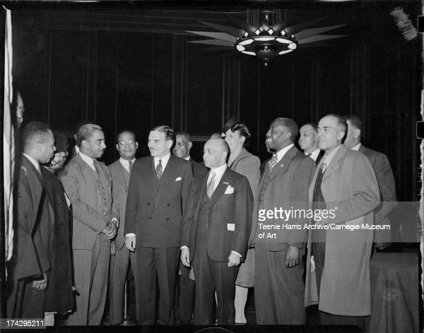Men including presidential candidate Thomas E Dewey wearing doublebreasted suit and Ira F Lewis near center standing in William Penn Hotel Pittsburgh...
