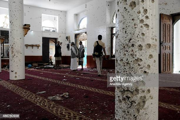 Men inspect the damage inside the AlMuayd Mosque after a deadly blast in capital Sanaa Yemen on September 03 2015 At least 20 people were killed and...