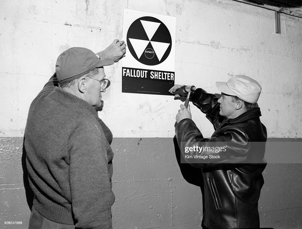 Men install fallout shelter sign in Chicago, ca. 1950 : News Photo
