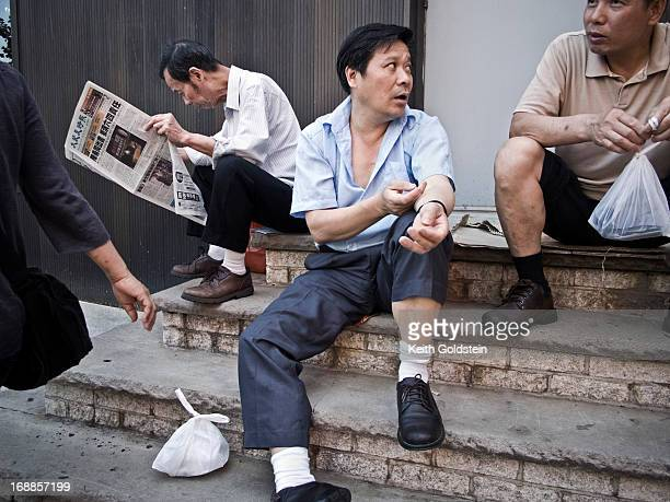Men involved in a conversation on the streets of Chinatown, New York City, New York.