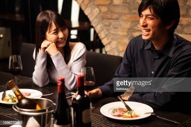 男性はガール フレンドとレストランでワインを飲む - ガールフレンド ストックフォトと画像