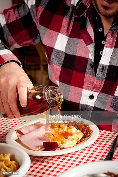 Men is pouring maple syrup