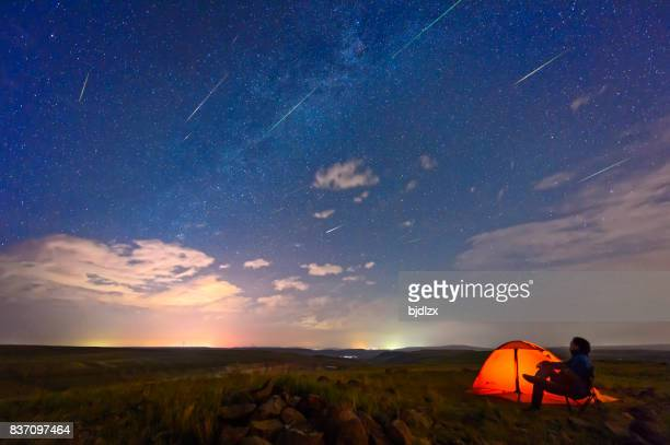A men is watching the Perseid meteor shower, on the edge of the tent.