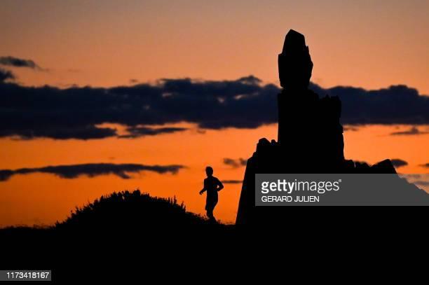 TOPSHOT A men jog next to the Le Bateau Ivre monument honouring French poet Arthur Rimbaud by sculptor Jean Adamo as the sun sets over the...
