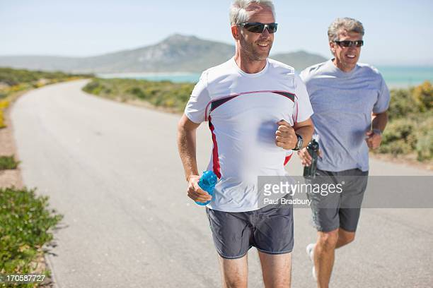 Men jogging and carrying water bottles