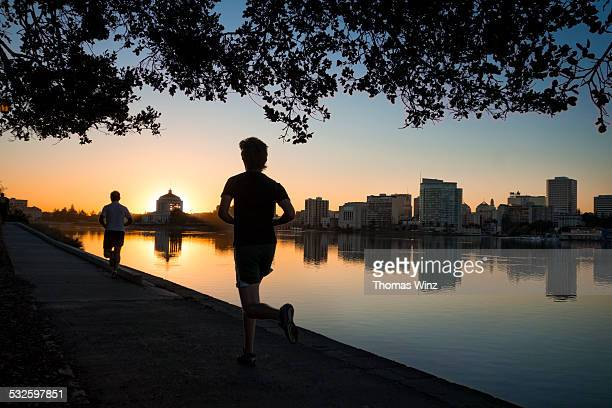 men jogging at lake merritt - oakland condado de alameda fotografías e imágenes de stock