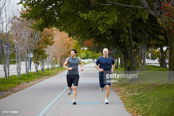 Men jogging on footpath in autumn city