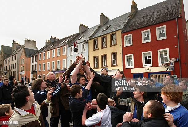Men jump to catch a leather ball at the start of the annual Fastern Eve Handba event on March 5 2009 in Jedburgh's High Street in the Scottish...
