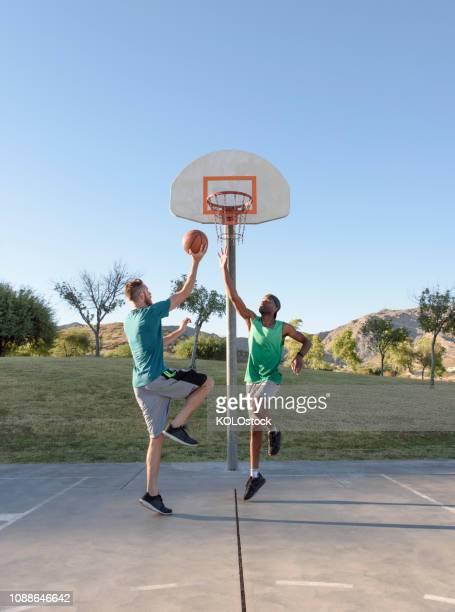 men jumping for basketball - デイフェンス ストックフォトと画像