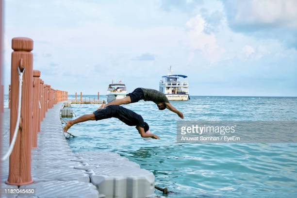 men jumping in sea against sky - anuwat somhan stock photos and pictures