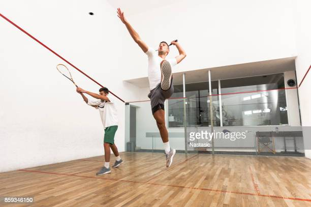 men jumping to hit a ball during squash match - racquet stock pictures, royalty-free photos & images