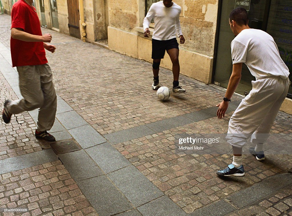 Men kicking soccer ball in street : Bildbanksbilder
