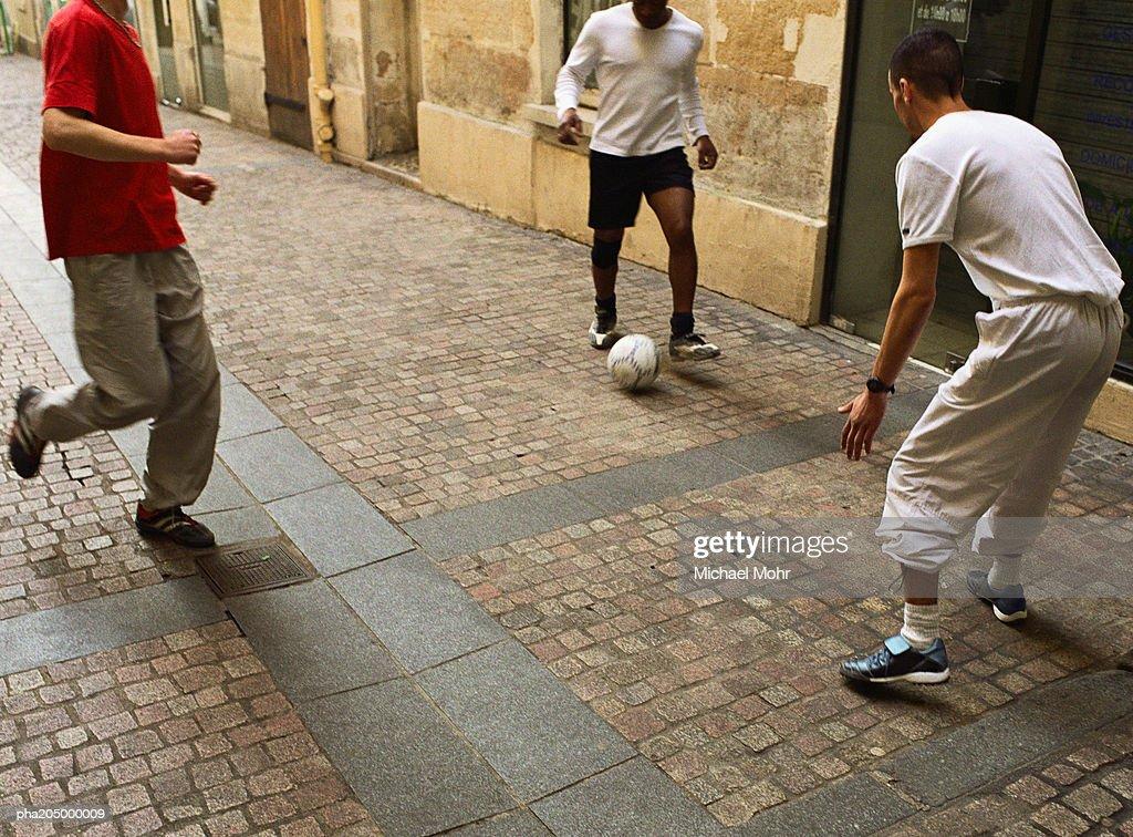Men kicking soccer ball in street : Stockfoto