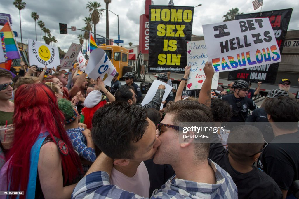 Men kiss in defiance of a counter protest from provocative street preachers at the #ResistMarch during the 47th annual LA Pride Festival on June 11, 2017, in the Hollywood section of Los Angeles and West Hollywood, California. Inspired by the huge women's marches that took place around the world following the inauguration of President Donald Trump and by the early pride demonstrations of the 1970s, LA Pride replaced its decades-old parade with the #ResistMarch protest to promote human rights by marching from Hollywood to West Hollywood.