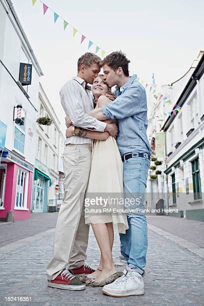 Men kissing woman on city street