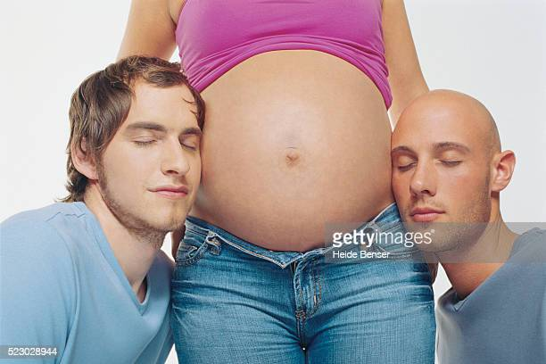 Men leaning against a pregnant woman's belly