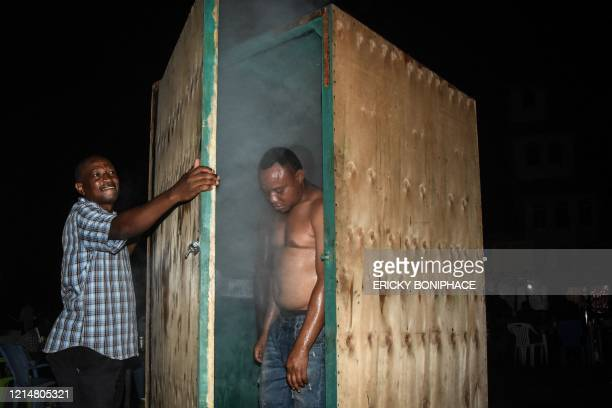 TOPSHOT Men leave the steam inhalation booth installed by Tanzanian herbalist Msafiri Mjema in Dar es Salaam Tanzania on May 22 2020 after using the...