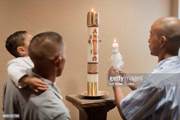 men lighting baptismal candle in church - godfather godparent stock pictures, royalty-free photos & images