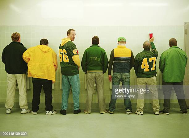 Men lined up at urinal, one looking back