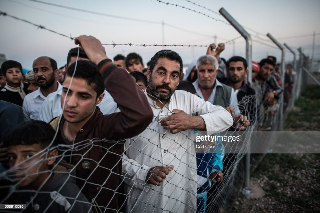 Men listen for their names to be called out by a camp official overseeing the return of refugees to recaptured parts of Mosul, in Khazir refugee camp on April 15, 2017 near Mosul, Iraq. Khazir camp, with a capacity of roughly 30,000 and along with several other camps near the city of Mosul, provides home for the approximately 300,000 people who have fled Iraq's second largest city as Iraqi government forces continue the military campaign to recapture the city from Islamic State who captured it in 2014.