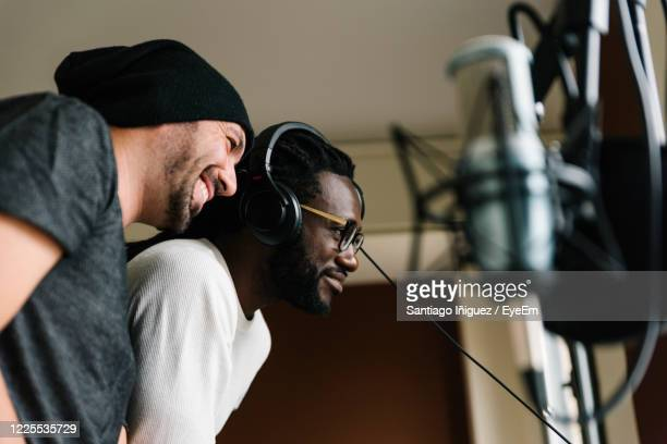 men listening music while standing in studio - singer stock pictures, royalty-free photos & images