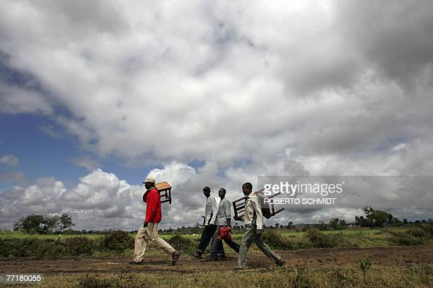 Men living in the Usa River village near Arusha Tanzania carry chairs and a flower arrangement to a gathering spot under a tree as they prepared for...