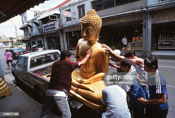 Men load a large Buddha statue onto the back of a pickup truck after it has been purchased from a shop selling Buddhist religious icons and other...