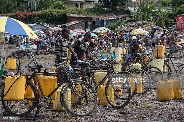 Men load bicycles with plastic tanks containing water from the Lake Kivu on the socalled People Beach in Goma That water is a wellknown transmitter...