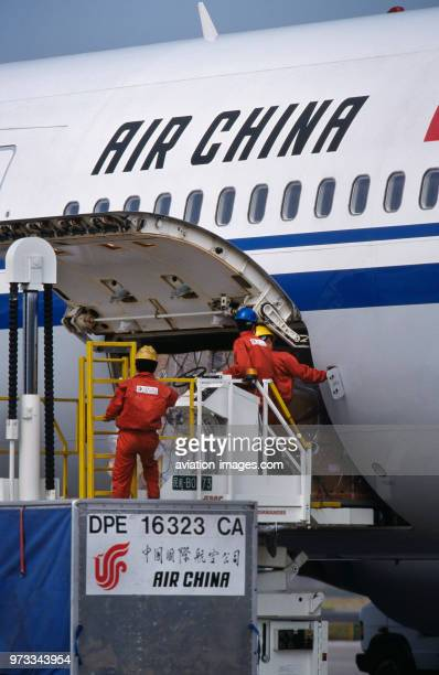 men loading cargo on a lowloader into an Air China International Boeing 767300