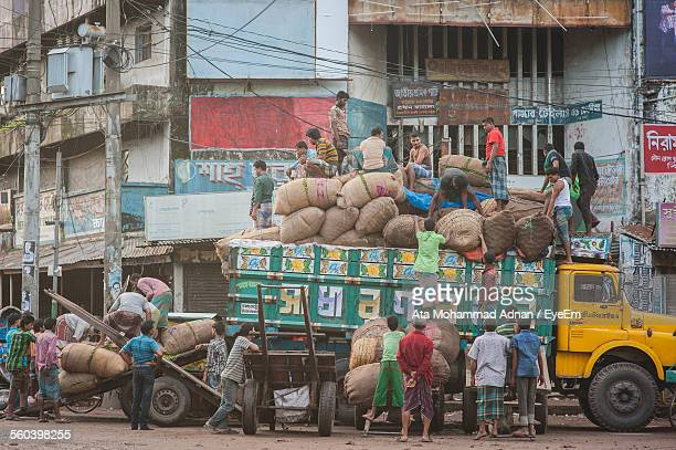 men loading sacks on truck against building - bangladeshi man stock photos and pictures