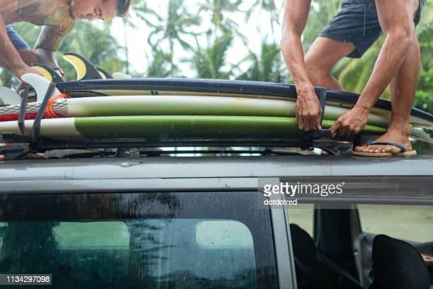 Men loading surfboards onto car roof rack, Pagudpud, Ilocos Norte, Philippines