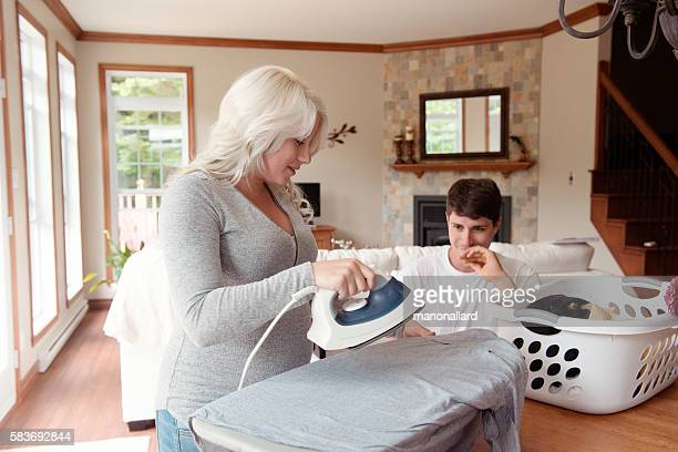 Men looging pregnant woman ironing clothes at home