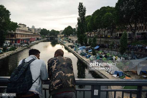 TOPSHOT Men look at a makeshift camp during its evacuation by police along the Canal de SaintMartin at Quai de Valmy in Paris on June 4 2018 More...