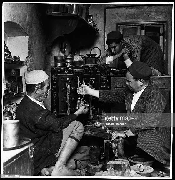 Men look at and feel the jewelry draped on the door of a safe at a jewel souk in Djerba an island with an ancient community of Jewish people