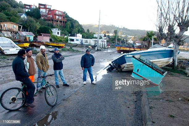 Men look at boats lying on the streets of Dichato 500 km south of Santiago on March 12 2011 hours after the place was hit by tsunami waves from...