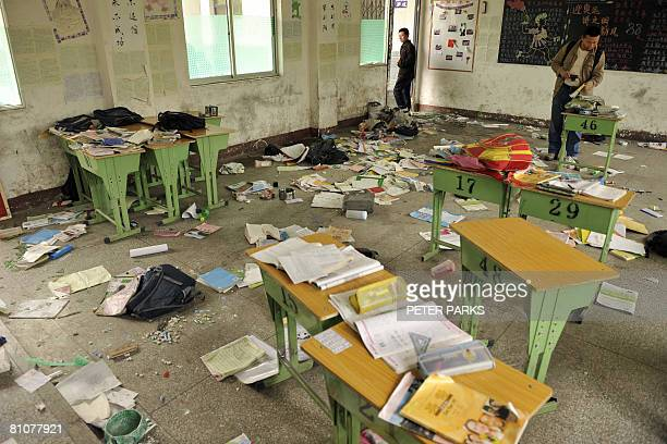 Men look at books papers and bags scattered inside a classroom in Dujiangyan on May 14 2008 after a powerful earthquake stuck in southwest China's...