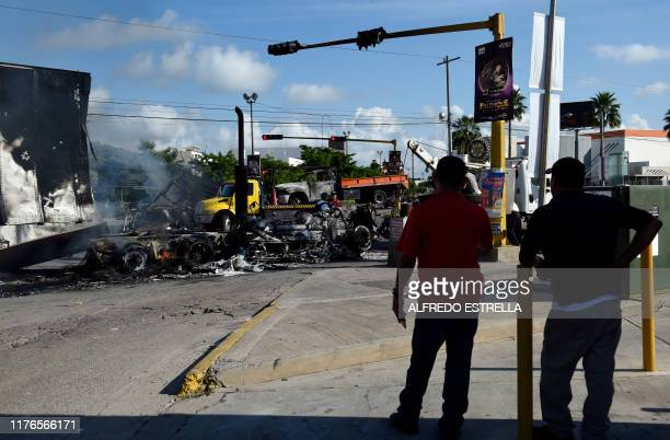 Men look at burnt vehicles after heavily armed gunmen waged an allout battle against Mexican security forces in Culiacan Sinaloa state Mexico on...