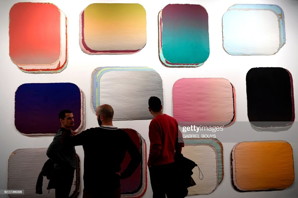 Men look at 'Coleccion de fondos' by Spanish artist Guillermo Mora Perez during the ARCO International Contemporary Art Fair opening in Madrid on February 21, 2018. Madrid hosts the annual Arco contemporary art fair, one of Europe's biggest, from February 21 to February 25, 2018. /