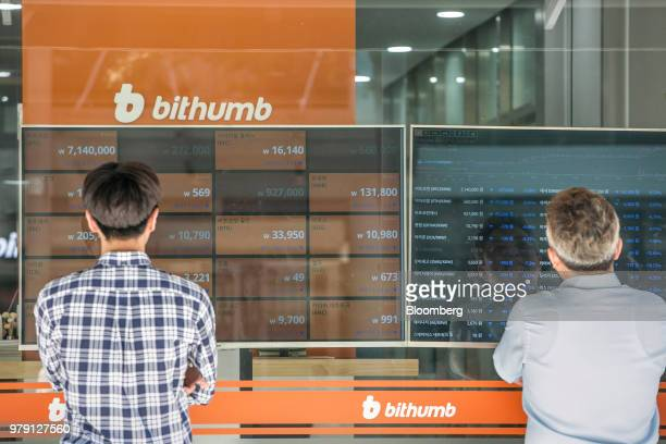 Men look at monitors displaying the prices of cryptocurrencies at a Bithumb exchange office in Seoul South Korea on Wednesday June 20 2018 Virtual...