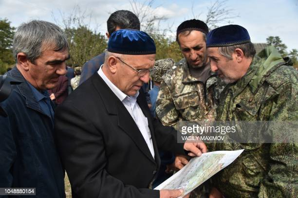 Men look at the map in Ingushetia's mountain village Dattykh close to the new border line between Chechnya and Ingushetia on October 10 2018...