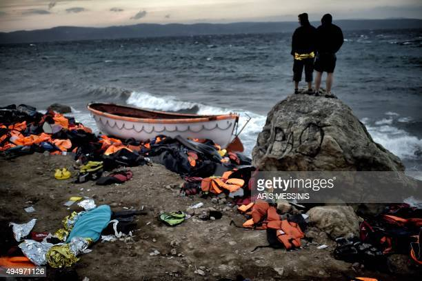 Men look at the sea next to the body of a man covered with a blue blanket lying on the beach on the Greek island of Lesbos on October 30 after a boat...