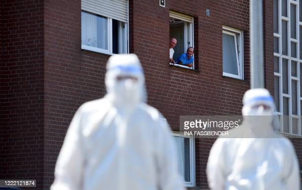 Men look on from a window to personell of a mobile testing unit of the German Red Cross and the German army , prior of testing the employees of the...