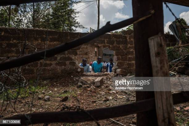 Men look through a hole in a wall created yesterday outside of a polling station in the Kibera slum on October 27 2017 in Nairobi Kenya Tensions...