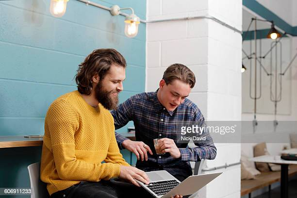 2 men looking at a laptop - all shirts stock pictures, royalty-free photos & images