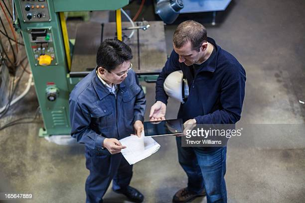 2 men looking at a tablet computer in a factory